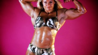 Huge female bodybuilder Brigita Brezovac flexing her bicep.